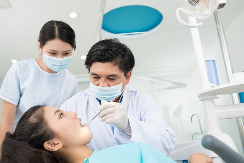 Bác sĩ kiểm tra tình trạng răng miệng cho bệnh nhân